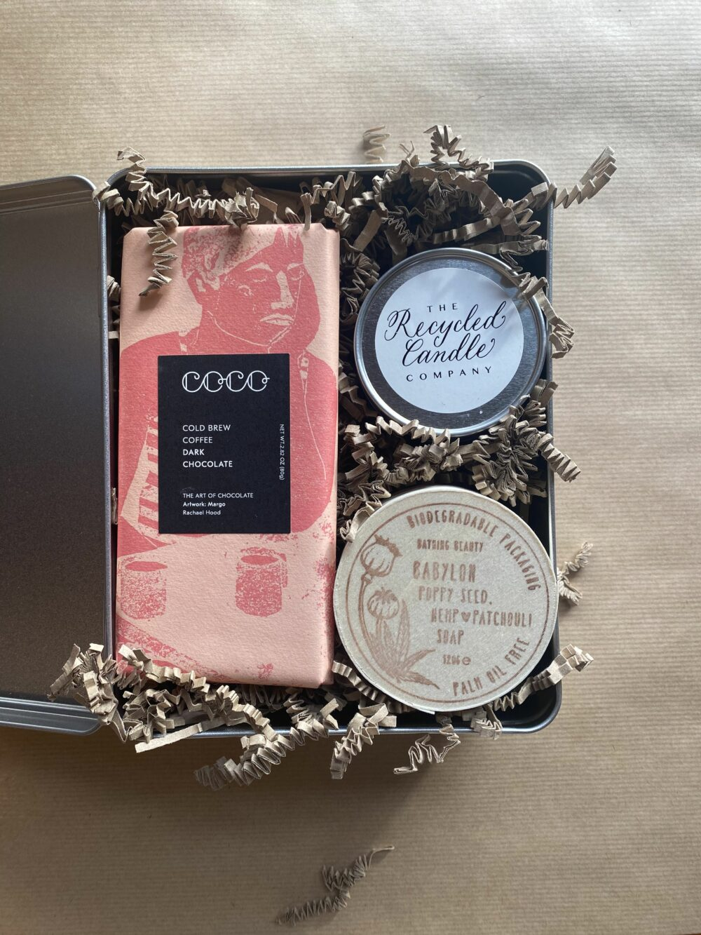 metal gift tin containing a bar of Cold Brew Coffee and Colobian single origin dark chocolate, Smoke scented recycled candle and patchouli scented, poppy seed studded, hemp oil enriched soap